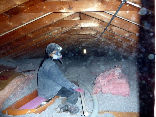 The pink fiberglass batt is being buried in the cellulose.  I don't want the batt on the attic floor because it will prevent the cellulose from conforming to the framing and wires, and I don't want it on top because I can't get the batts to sit tightly against each other.  So, I blew a layer of cellulose, put the batt on top, then blew more cellulose, which filled the spaces around the batt.  I had hoped adding fiberglass batts into insulation would reduce the amount of cellulose I needed to install, but I ended up using 221 bails.